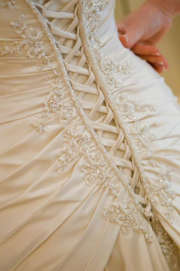 Wedding dress detail: lacing, pleating and embroidery