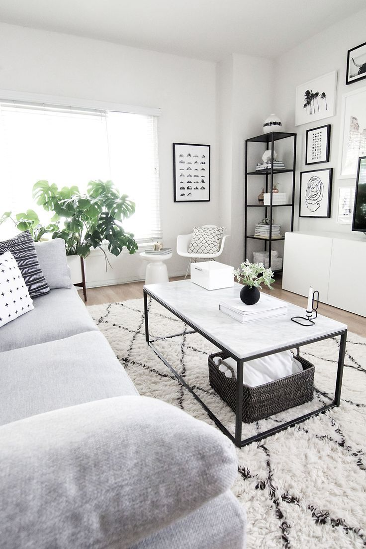 Idée décoration et relooking Salon Tendance Image Description Monochrome living room neutral space black and white frames indoor plants grey couch sofa natural light west elm rug