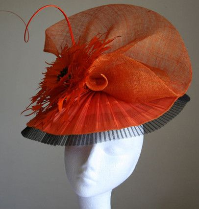 Orange headpiece with crinoline, feather flower and quill.