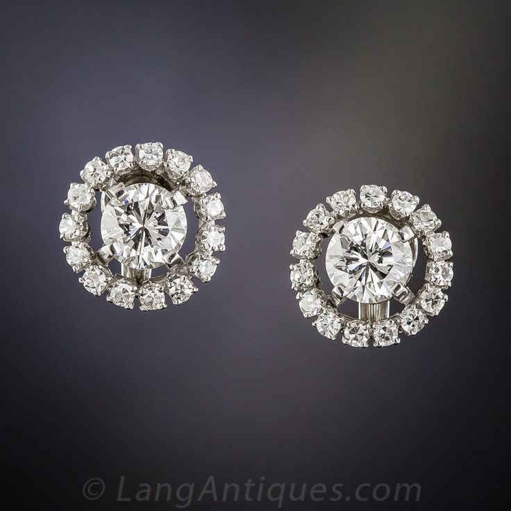 More fun and more sparkle than simple studs. A bright white pair of high-quality round brilliant-cut diamonds, together weighing 1.50 carats, are orbited by glittering platinum and diamond rings in these big, glittering earrings, measuring just shy of a half-inch across.