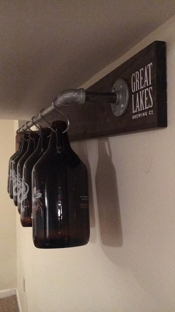 Looking for the PERFECT GIFT for the craft beer lover in your life? Get this just in time for Thanksgiving, Christmas, Birthdays or just because!  A Modern, Industrial and Rustic addition to your home – allowing for a full view of each half gallon growler jug! This unique growler rack is the perfect storage solution to getting your growler jugs off the counter, keeping your bar area clean and glass growler jugs safe until you refill them!  Handmade with quality pine wood (stained dark…
