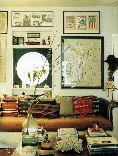 Mismatched pillow patterns. Love the art and coffee table accessories.