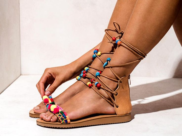 Piccolo  Multi-colored macrame friendships, wooden beads, hand-painted ceramic evil eyes, yellow and hot pink pom poms.  Get the experience: http://www.elinalinardaki.com/shoes/sandals/new-collection/sandal-piccolo/