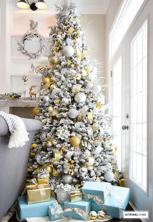 A silver and gold Christmas tree is surrounded by presents wrapped in Tiffany blue wrapping paper stands behind a gray roll-arm sofa.