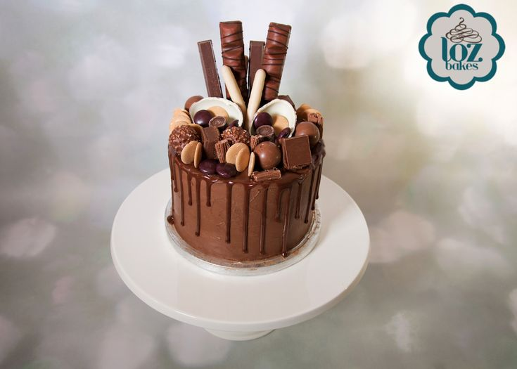 "A 6"" chocolate drip mud cake, piled high with #chocolatecaramelshortcakes #kinderbars #cadburyfingers #kinderegg #ferrerorocher #lindtballs #caramacbuttons #cadburyflake #galaxyminstrels #rolos"