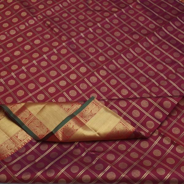 A bed of crushed rubies forms the silk canvas, smothered with close-knit gold checks playing host to gold dots. The sari gives the appearance of swirling Burgun