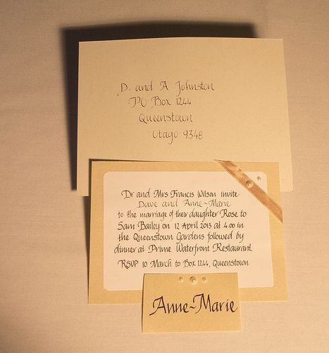 Wedding invitation, envelope and place card in matching stationery with calligraphy handwriting.