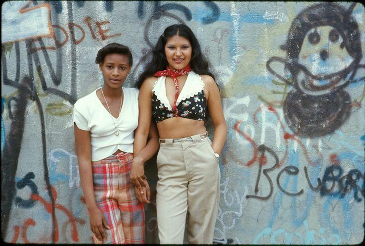 1974. Две латинос позируют перед стеной, изгаженной граффити в Бруклине, Нью-Йорк