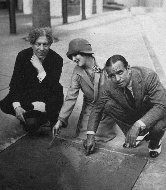 Mary Pickford and Douglas Fairbanks in front of Grauman's Chinese Theatre immortalising their hand/footprints (1927)