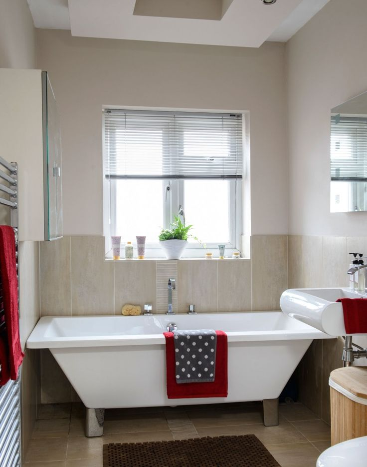 neutral modern bathroom with feature suite and stone tiles