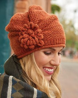 The knitted bloom on this lovely topper will brighten even the darkest winter day. The flower embellishment is worked separately and sewn in place after the cloche is gathered on the side. A simple slip-stitch pattern adds pretty texture to the crown.