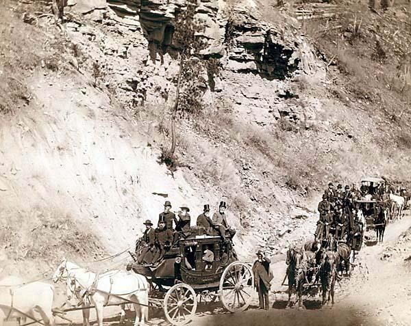 Omaha Board of Trade in Mountains near Deadwood, April 26, 1889. It was created in 1889 by Grabill, John C. H., photographer. The picture presents Procession of stagecoaches loaded with passengers coming down a mountain road.: