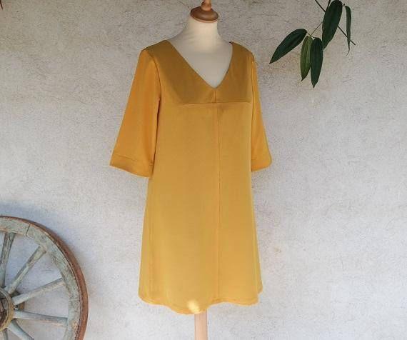 Robe trapèze ample réalisée avec un tissu un crêpe de polyester jaune. Cette robe est simple avec un décolleté avec une pointe en V. La robe est doublée en voile de coton. Sa forme ample cache toutes les imperfections du corps. Elle est agréable à porter en toutes occasions (bureau, soirée, …) et en toutes saisons avec des chaussures plates ou à talon. Deux pinces poitrine. Longueur de la robe = 100 cm à confirmer à la commande. Le modèle présenté est une taille 40. Elle peut être réalis...