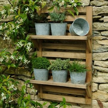 This wall-mounted herb rack looks so nice with the stone wall. If only I had the space! #herbs #gardening
