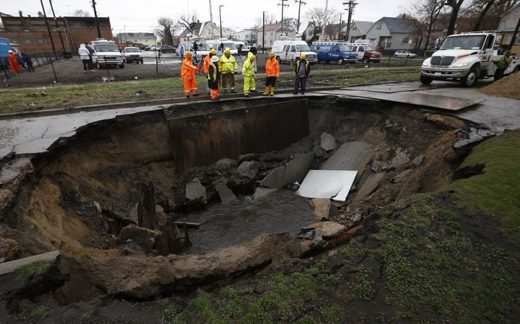 Workers look into a sinkhole caused by a broken water main in Chicago, Illinois, April 18, 2013.  Heavy rains and flooding brought havoc to the Chicago area on Thursday, shutting major expressways, delaying commuter trains for hours, cancelling flights, flooding basements and closing dozens of suburban schools. On the city's South Side, a sinkhole opened up on a residential street, swallowing three cars, according to Officer Mike Sullivan of the Chicago Police Department. One person was…