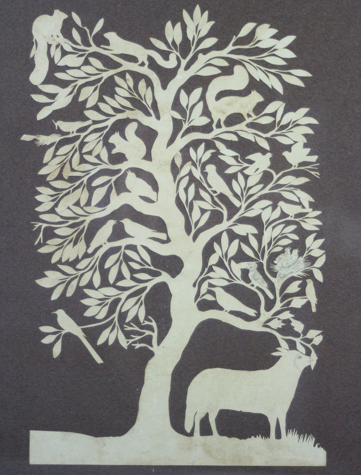 A fragile paper cutout featuring a tree with animals. The entire white portion is intricately cut from a single piece of paper and laid on a dark backing board.