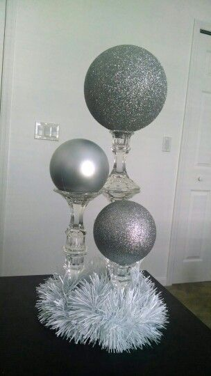 DIY Dollar Tree candlesticks. 2 glued together for medium height, and 3 for the tallest. Place large ornaments on top, or paint Styrofoam spheres. Voila! Inexpensive Winter Wonderland wedding decor! Short centerpieces