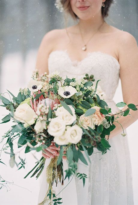 Brides.com: 18 Wintry Wedding Bouquets A winter wedding bouquet made of white roses and anemones, lush greenery, and berries, created by Holly Bryan Floral And Botanical Design. Photo: Laura Leslie Photography and Gracie Blue Photography