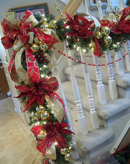 Garland staircase decoration.  I like the red and gold together and the use of the bead strand beneath the garland.