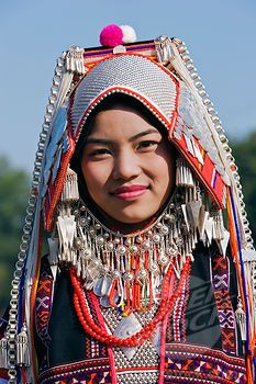 Myanmar, Burma, Kengtung. An Akha woman wearing traditional costume with a headdress of silver and beads. | © John Warburton Lee