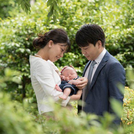 緑の中に囲まれて赤ちゃんを抱く夫婦