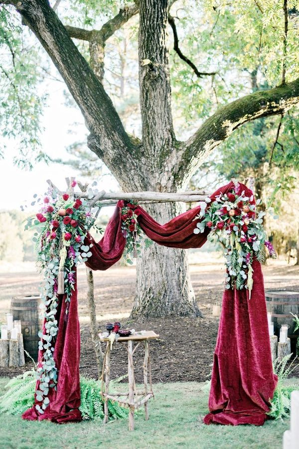 Red Wedding Decorations: Dress up your ceremony altar with a beautiful arch draped in red velvet. It gives a regal look that would perfectly suit a formal red wedding in the winter.   Gorgeous Ideas for a Red Wedding Palette