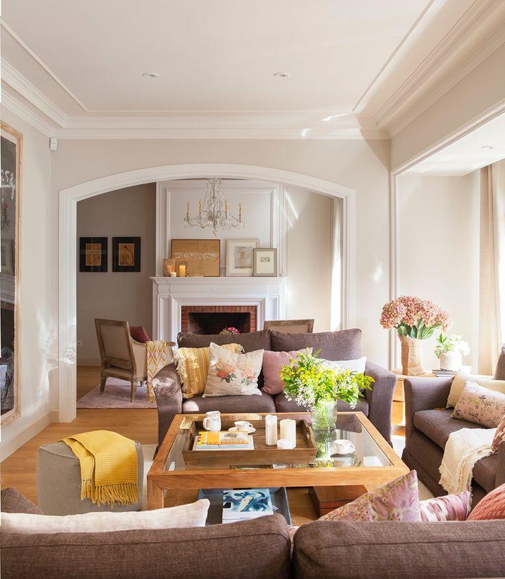 Salón con mesa de centro, sofás, chimenea al fondo y arco_Pano10483-10484