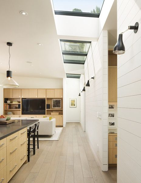 A painted wood wall marks the boundary between the home's public and private wings. Linear skylights bathe the open-plan communal area in light.