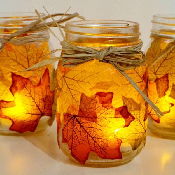Kerzen in Gläsern, dekoriert mit gelben Blättern