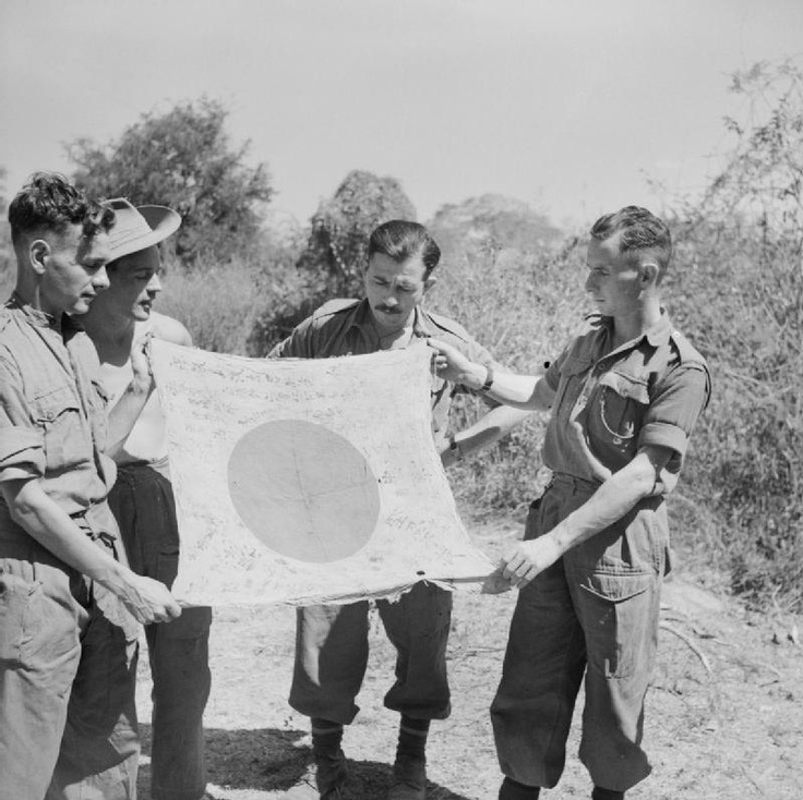 British troops show off a souvenir Japanese flag captured at Ondaw, Burma, 12 February 1945.