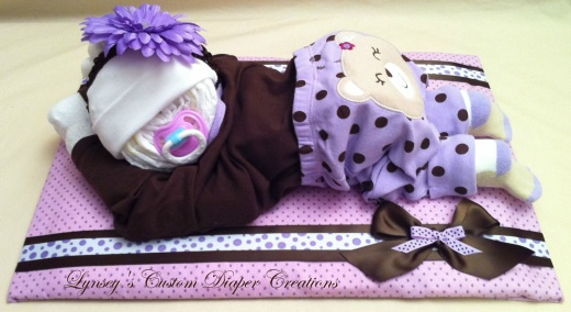 Really cute~I've done them (diaper baby) before but they've sitting up.  Never thought of laying them down!  could lay them on  a bow holder for girl.  oh the possibilities!