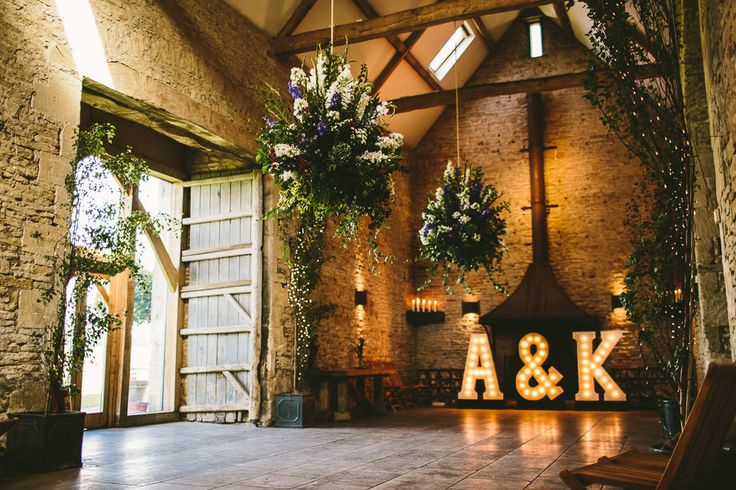 Cripps Stone Barn in the Cotswolds - Claire Pettibone lace dress in a rustic barn wedding in the Cotswolds with red bridesmaid dresses. Groom wears a Reiss Suit with floral bow tie and light up letters decoration.