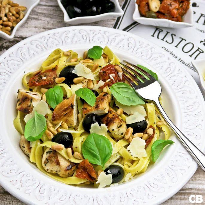 Pasta met gegrilde kip en semi-gedroogde tomaatjes. Alle mediterrane ingrediënten van dit gerecht-de beetgare pasta, de stukjes gemarineerde en daarna krokant gegrilde kip, de sappige semi-gedroogde tomaatjes, de lichtzoute zwarte olijven, de geroosterde pijnboompitten, de versgeraspte Parmezaanse kaas en de frisgroene blaadjes basilicum - vormen samen een match made in heaven!