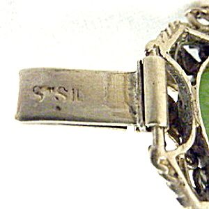 Misattributed to Dorothy Wager. Not by her. Arts and Crafts sterling silver and chloromelanite bracelet. Bracelet is stamped Stg Sil. to clasp. It measures about 18.5 cm long (7.1/4 inches), and is 1.85 cm wide (3/4 inch). Each stone is 1.5 cm diameter (5/8 inch). Fitted with a safety chain. View 5/5.