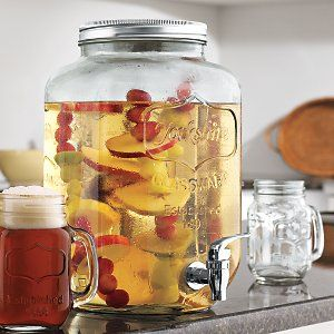 """Mason Jar Beverage Dispenser $24.99 Crafted from high quality, durable glass fashioned into the shape of a mason jar complete with a traditional tin screw off lid and easy pour spigot.   Mason jar beverage dispenser measures 12.5"""" height x 9.5"""" Width x 7.5"""" Depth and holds approximately 2 gallons of your favorite drinks and cocktails."""