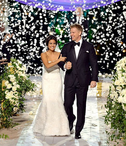Sean Lowe and Catherine Giudice from the Bachelor (Season 17) walk down the aisle under rose petal confetti with draped floral arrangements as aisle decor.