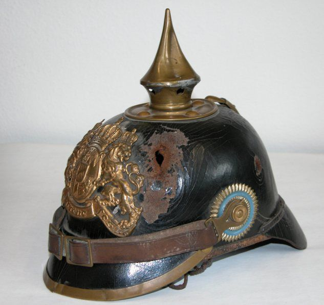 """Pickelhaube of a soldier of K.B.IR 16. The owner was wounded in 1914. A piece of shrapnel pierced Pickelhaube and skull and brain before exiting on the other side. The owner survived the terrible wound and died in 1977. (Exhibit in """" Haus der Bayerischen Geschichte"""" - Regensburg"""
