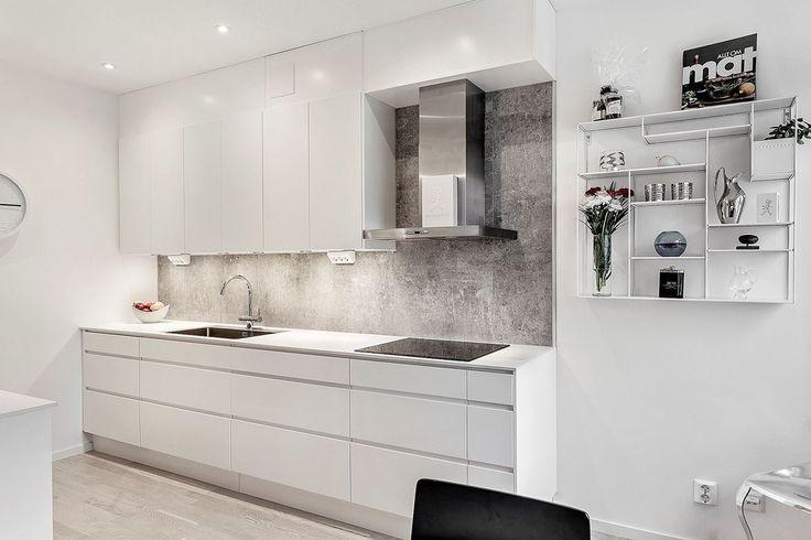Stilrent kök från Ballingslöv med goda förvaringsmöjligheter bakom vita handtagslösa luckor. Elegant kakel samt spotlights ovan arbetsytor, kompaktlaminat med undermonterad ho.