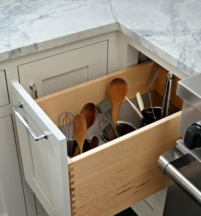 Beside a stainless steel stove, a white shaker cabinet finished with a polished nickel pull pulls out to reveal a utensils drawer fitted with three built in polished nickel cups perfect for both large and small kitchen utensils.