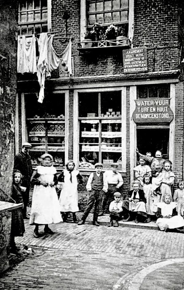 Blindemansteeg 19 in de Duivelshoek. Water-en-vuur winkeltje De Morgenstond. Boven de deur een bord met reclame voor poppenspeler A.A. van Hemert.  De Duivelshoek werd gesloopt voor o.a. de bouw van het Tuschinski-theater in 1919.  A.J. Nuss, ca. 1900.
