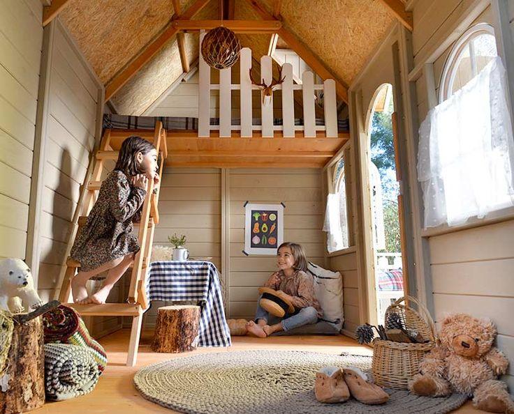 Interior de casita de madera para niños con terrazaTIROL, con litera con escalera y barandilla de seguridad.