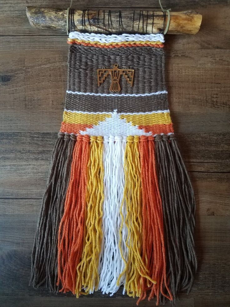 This is a woven wall hanging done on a 70's retro color yarn pallet with a metal thunder bird as the center accent by MacuNana