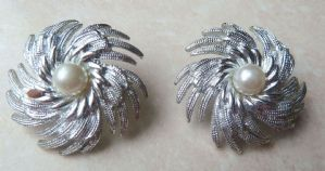 A vintage pair of Sarah Coventry ' Pinwheel ' design earrings.  These are clip on earrings, with a central pearl and a textured and polished metal design.