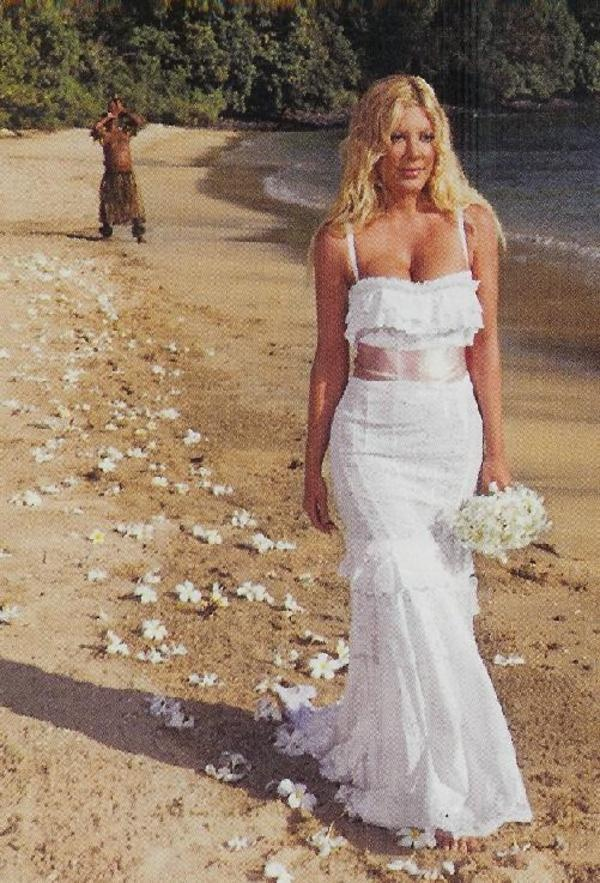 Tori Spelling and Dean McDermott married in a secret ceremony on May 7, 2006 in Fiji. No family or friends were present. Tori walked barefoot across the beach in a white eyelet Dolce & Gabbana dress with a pink sash. She held a bouquet of white orchids with stamp-sized photos of Dean's deceased parents and her former nanny. A pathway of fragrant white frangipani petals led her to Dean, who stood waiting in a white Dolce & Gabbana suit.