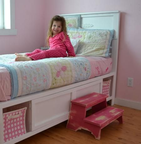 An easy to build storage bed featuring a footboard and headboard, four cubbies perfect for fabric bins, and four large shelves perfect for hiding bedtime books. Easily customizeable to a full size.