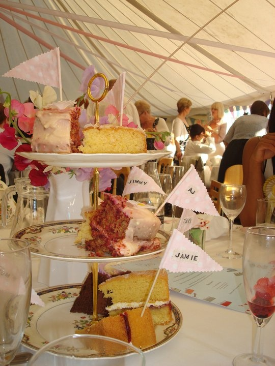 Cakes on homemade cake stands with all crockery and plates collected from charity shops.