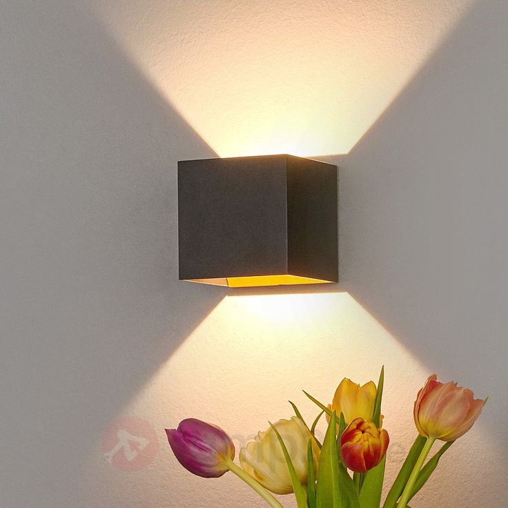 Svart LED-vägglampa som er guldfärgad på insida