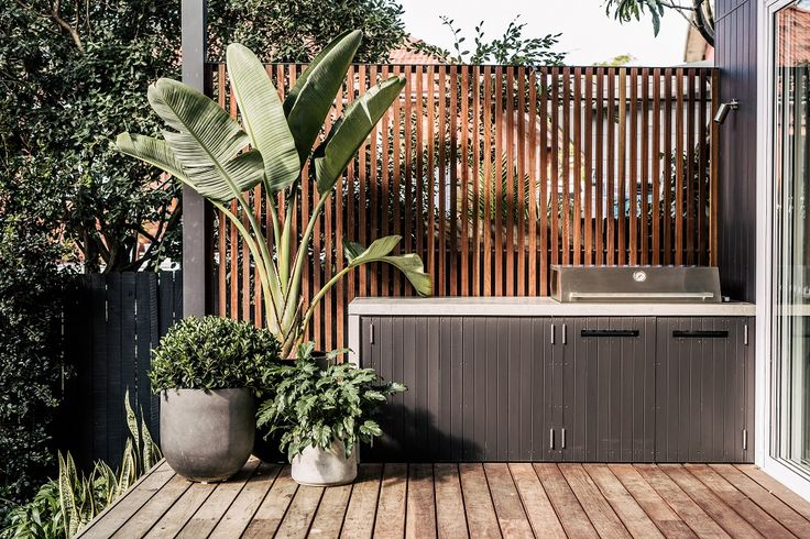 The built-in BBQ with a polished concrete bench top is set in front of a vertical Spotted Gum screen with copper spaces were used to separate the batons.