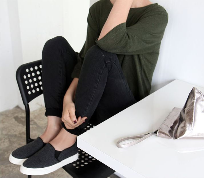 Green sweater, charcoal skinny jeans, grey slip-ons, metallic clutch.