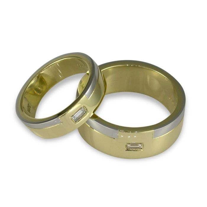 DIAMOND WEDDING SET. 18ct yellow gold flat band with a platinum strip, each set with a Baguette Diamond.